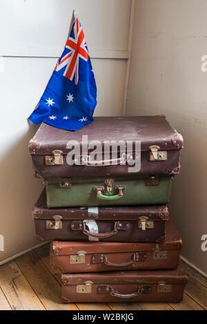 Australia, Victoria, VIC, Bonegilla, The Bonegilla Migrant Experience Museum, post-WW2 immigrant facility, housing barracks interior, luggage and Australian flag - Stock Photo