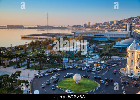 Azerbaijan, Baku, View of traffic at roundabout on Neftchilar Ave, looking towards Baku bay, Venezia restaurant, the Carpet museum, in the distance is Baku Crystal Hall, where the 2012 Eurovision Song Contest was held - and the World's second Tallest Flagmast - Stock Photo