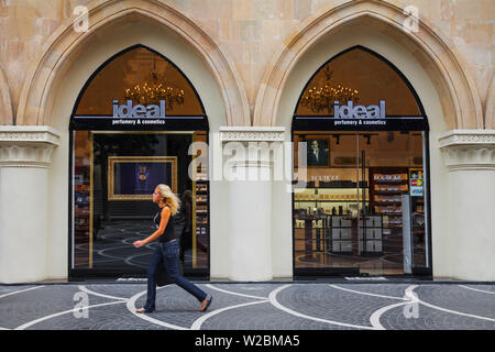 Azerbaijan, Baku, Nizami (Torgovaya) St -  a pedestrian street in the center of Baku, Woman walking past Ideal perfumery and cosmetics shop - Stock Photo