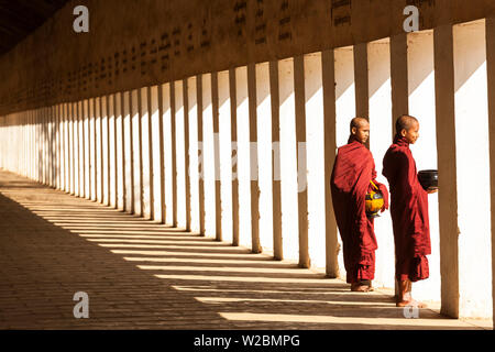 Monks in walkway to Shwezigon Pagoda, Bagan (Pagan), Myanmar (Burma) - Stock Photo