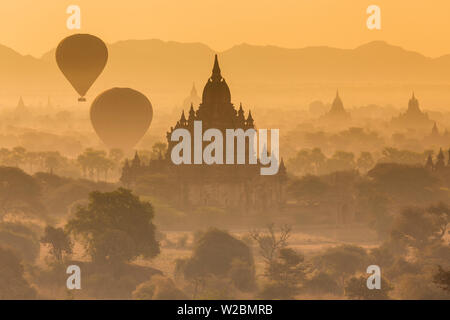 View of the pagodas and temples of the ancient ruined city of Bagan (Pagan), & balloons at sunrise, Myanmar, (Burma) - Stock Photo