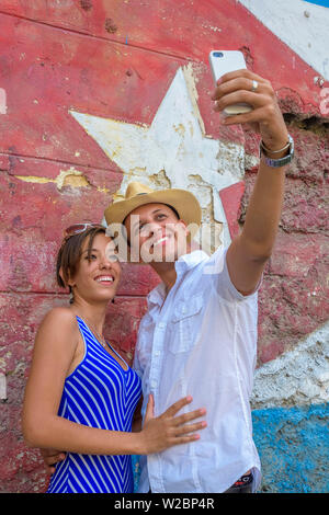 Cuba, Havana, Tourist couple taking a selfie in front of mural - Stock Photo