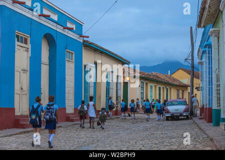 Cuba, Trinidad, Children walking past Classic American car on way to school - Stock Photo