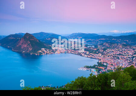 Elevated view over Lugano from Monte Bre illuminated at sunrise, Lugano, Lake Lugano, Ticino, Switzerland - Stock Photo