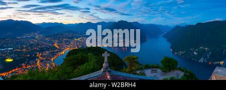 Elevated view over Lugano from Monte San Salvatore illuminated at Dusk, Lake Lugano, Ticino, Switzerland - Stock Photo
