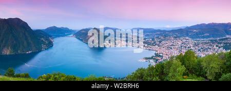 Elevated view over Lugano from Monte Bre illuminated at sunrise, Lugano, Lake Lugano, Ticino, Switzerland - Stock Photo