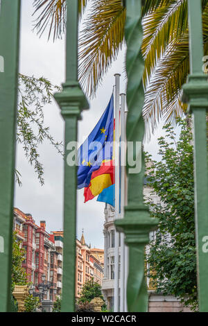 Flags of the European Union, Spain, Asturias Region on the facade of an ancient building behind a green fence grid. Against the green branches of palm - Stock Photo