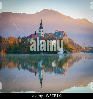Bled Island (Blejski otok) with the Church of the Assumption (Cerkev Marijinega vnebovzetja) & Bled Castle illuminated at Sunrise, Lake Bled, Bled, Upper Carniola, Julian Alps, Slovenia - Stock Photo