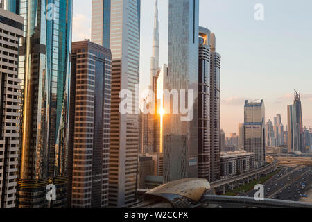 Elevated view over the modern Skyscrapers & metro station along Sheikh Zayed Road looking towards the Burj Kalifa, Dubai, United Arab Emirates - Stock Photo