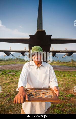 Vietnam, DMZ Area, Quang Tri Province, Khe Sanh, Former Khe Sanh US Combat Base, museum, former US Air Force, C-130 Hercules, transport plane and man selling war souvenirs - Stock Photo