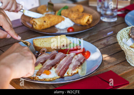 Fried eggs with bacon, cheese and bread for breakfast in European cafe. - Stock Photo