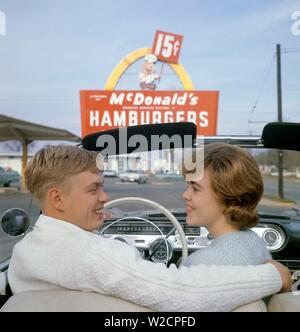 Fast food in the 1950s. A young couple in their convertible car with a McDonald's sign in the background. The yellow arch being part of the original design called the Golden Arches was first used 1953.  The cost of a limited menu hamburger, shake and fries was 15 cents. 1950s 1960s ref 5-40-4 - Stock Photo