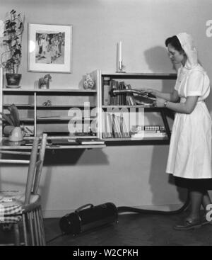 Vacuuming in the 1950s. The young student Gertrud Larsson is having a cleaning day in her student apartment. She is thorough and even the books in the bookshelf gets a good vacuum cleaning. Sweden 1954 - Stock Photo