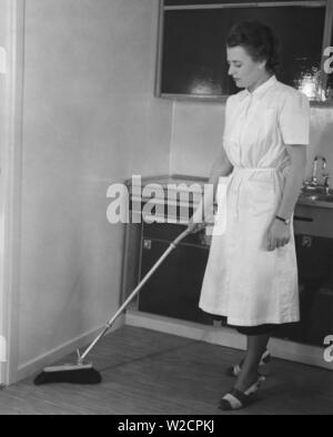 Cleaning day in the 1950s. A young woman dressed in a practical cleaning outfit,  is cleaning the kitchen and is using a brush with an telescoping handle. A new invention to stand up straight when dusting and avoid back pains. Sweden 1050 - Stock Photo