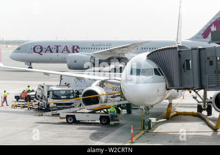 Hamad International Airport, Doha, 2018-05-01: Two Qatar airline airplanes at the airport. Jetway at the plane, front view. The working day at airport - Stock Photo