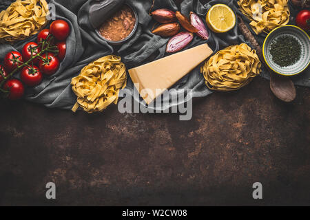 Italian food ingredients for pasta with tuna tomatoes sauce, top view. Copy space. Pasta,parmesan, open tuna can, tomatoes, onion, lemon on dark rusti - Stock Photo