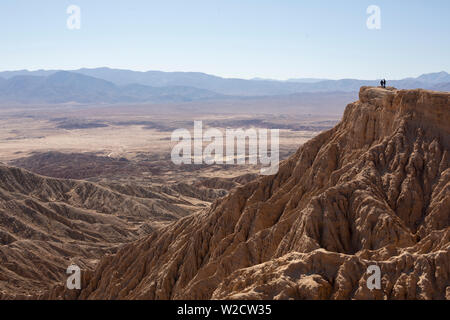 Two figures standing at inspiration point over badlands - Stock Photo