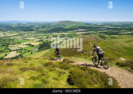 Two male cyclists on mountain bikes biking down a path on Longside Edge from Skiddaw in Lake District National Park. Keswick Cumbria England UK - Stock Photo