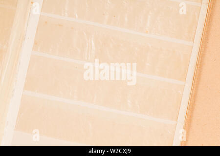 Closed old book for postage stamps isolated on brown background - Stock Photo