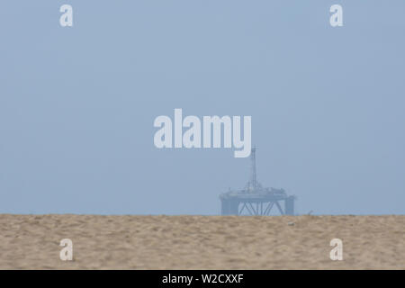Ocean Oil Platform Over Beach Sand Dune - Stock Photo