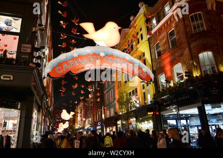London/UK - November 28, 2013: Carnaby street in London decorated for Christmas with red banners and birds, making the perception more happy. - Stock Photo