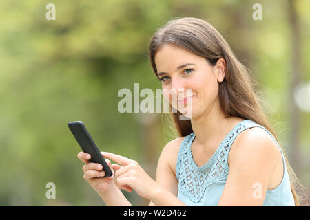 Smiley woman holding smart phone looking at you in a park with a green background - Stock Photo