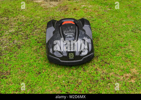 Nagoya, Japan - Jun 29, 2019. Automatic lawn mower robot moves on the grass at botanic garden. - Stock Photo