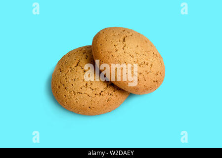 Two fresh oatmeal cookies on a blue background - Stock Photo