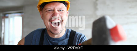Angry builder holding sledgehammer and