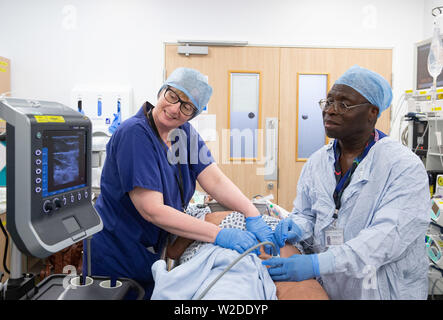 An Anaesthetist and nurse study the patient's intestine on a monitor in the pre-operation room in an NHS Hospital. - Stock Photo