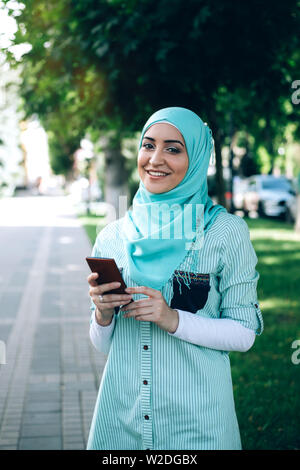 Beautiful muslim woman using smartphone at street. - Stock Photo