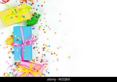Colorful Gift boxes, paper confetti and twirled party serpentine on a white background with copyspace, greeting card and party invitation template des - Stock Photo