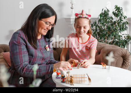 Teen girl on reception at the psychotherapist. Psychotherapy session for children. The psychologist works with the patient. The girl plays toy animals - Stock Photo