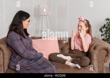 Teen girl on reception at the psychotherapist. Psychotherapy session for children. The psychologist works with the patient. Girl smiling sitting on a - Stock Photo