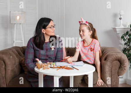 Teen girl on reception at the psychotherapist. Psychotherapy session for children. The psychologist works with the patient. The girl draws pencil with - Stock Photo