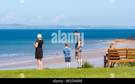 John Muir Way, East Lothian coast, Scotland, United Kingdom, 8th July 2019. UK Weather: Lovely warm sunshine on the coastline with people enjoying the outdoors on Gullane beach. A family enjoys the view overlooking Gullane Bents at low tide along the John Muir Way - Stock Photo