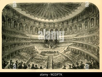 """'Interior of the Albert Hall', c1876. Royal Albert Hall is a concert hall in South Kensington, designed by civil engineers Francis Fowke and Henry Y. D. Scott, opened by by Queen Victoria in 1871 who laid the foundation stone in 1867, in memory of her husband, Prince Albert. From """"Old and New London: A Narrative of Its History, Its People, and Its Places. The Western and Northern Studies"""", by Edward Walford. [Cassell, Petter, Galpin & Co., London, Paris & New York] - Stock Photo"""