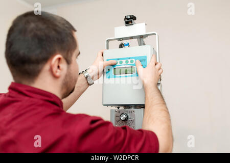 The doctor radiologist sets up an old veterinary X-ray machine before work at a veterinary hospital. - Stock Photo