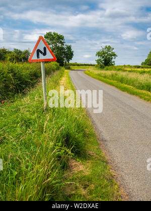 Twisty road ahead zig zag sign at the side of a single track country road - Stock Photo