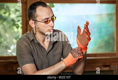 Young man in glasses wearing protective gloves - Stock Photo