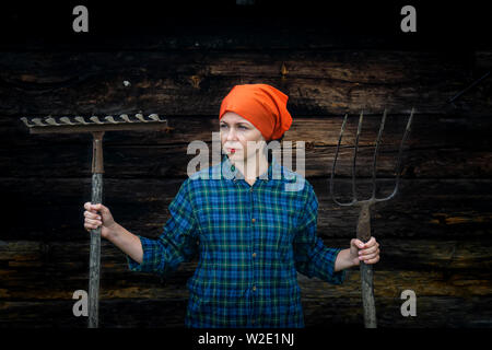 Young woman stands with a pitchfork near a stable on a ranch - Stock Photo