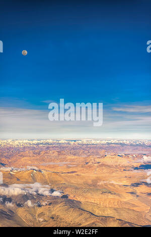 Full moon over the barren mountains of the Zanskar range of inner Himalayas, India. Taken from a plane on an early July morning. Portrait orientation. - Stock Photo