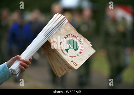 Russia. 07th July, 2019. PSKOV REGION, RUSSIA - JULY 7, 2019: A person holds souvenir flags during the 60th Kurgan Druzhby meeting attended by Soviet Army veterans and guerrillas who fought against Nazi Germany during the Great Patriotic War (part of WWII) in 1941-1945 and who now live in Russia, Belarus and Latvia. Vladimir Smirnov/TASS Credit: ITAR-TASS News Agency/Alamy Live News - Stock Photo