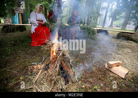 Russia. 07th July, 2019. PSKOV REGION, RUSSIA - JULY 7, 2019: Women in traditional clothes sit by a bonfire during the 60th Kurgan Druzhby meeting attended by Soviet Army veterans and guerrillas who fought against Nazi Germany during the Great Patriotic War (part of WWII) in 1941-1945 and who now live in Russia, Belarus and Latvia. Vladimir Smirnov/TASS Credit: ITAR-TASS News Agency/Alamy Live News - Stock Photo