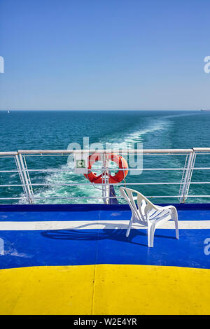 A plastic chair on the rear deck of a cross channel ferry coming into the UK from Brittany - Stock Photo