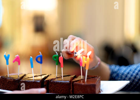 The girl is preparing for the holiday, decorating cakes. - Stock Photo