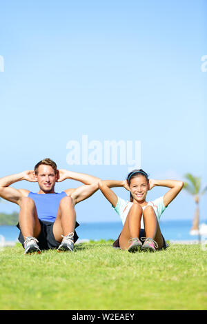 People exercising - Couple doing sit ups outdoors. Fitness couple doing situps exercise during outside cross training workout. Happy young multiracial couple, Asian woman, Caucasian man. - Stock Photo