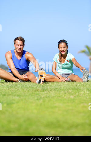 Fitness people - couple stretching exercises outdoors. Fit woman and man doing hamstring leg stretch exercise and stretches workout outdoor in summer. Beautiful multiracial couple. - Stock Photo