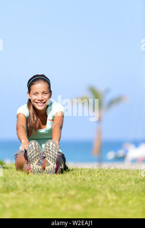Fit fitness woman doing stretching exercises outdoors. Girl doing hamstring leg stretching exercise and stretches. Female sports model exercising outdoor in summer. Beautiful multiracial Asian girl. - Stock Photo