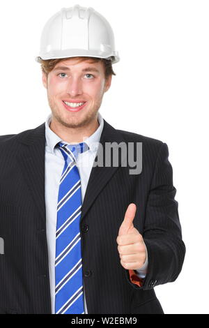 Engineer or architect in suit showing successful thumbs up. Male business man wearing white hard hat signalling success hand sign smiling happy. Portrait of male engineer isolated on white background. - Stock Photo